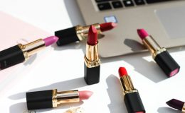 multiple lipsticks laying on the table next to a laptop